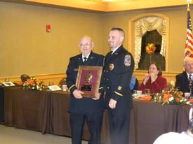 Les Hansen receiving his 60 years of service award from outgoing Fire Chief Shawn Downs.