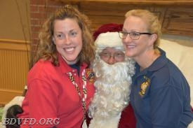 Two of our own little elves (Jamie Olson and Cristy Bixby) giving  Santa (Gary Hanbury) a wonderful surprise.