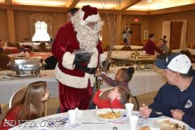 Santa makes the rounds. See the little girl asking him about his belt.
